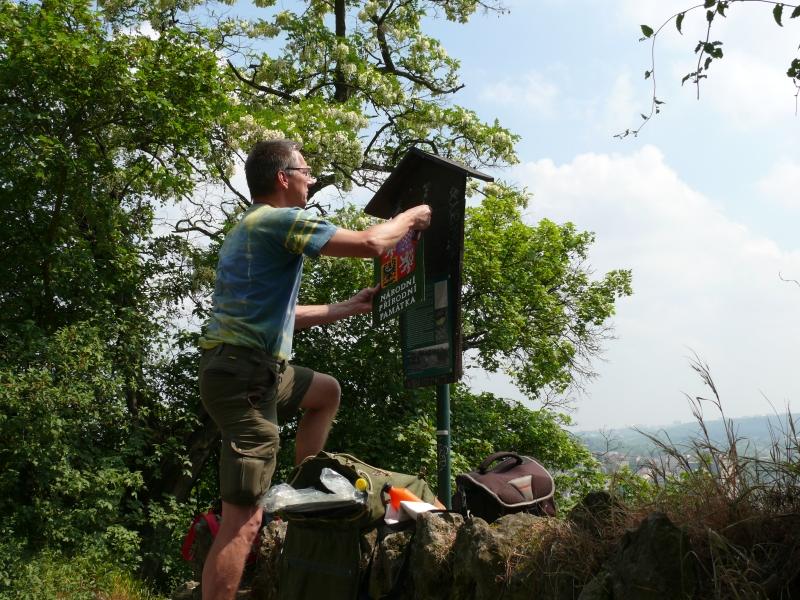 Strážce přírody při výměně smaltované tabule na hraničníku