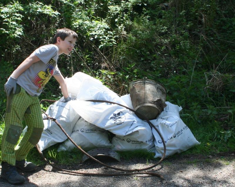 Brigádník u pytlů s posbíranými odpadky
