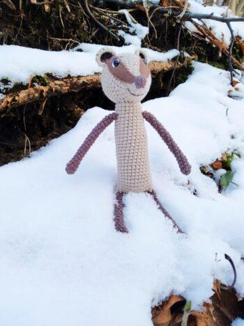 Háčkovaný jezevec na sněhu u své nory